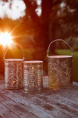 Candle lanterns made from recycled tin cans with perforated patterns