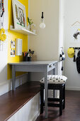 Grey desk on bench against yellow wall
