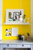 Shelf on yellow wall above grey desk