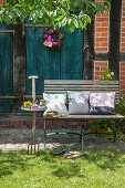Cushions on bench outside house with petrol-blue wooden doors