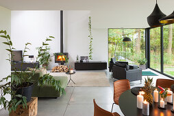 Dining table in modern, open-plan interior with glass wall