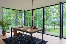 Desk opposite glass wall overlooking garden in architect-designed house