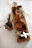 Bohemian-style arrangement of sticks, wooden candle holders and dried flowers