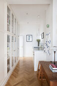 Fitted cupboards with glass doors in rustic white kitchen