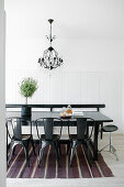 Black metal chairs around table on striped rug in dining room