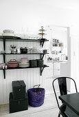 Crockery on black shelves in dining room next to kitchen doorway