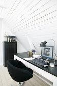 Black swivel chair at desk below sloping wall