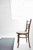 Old chair on white floor below skylight
