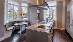 Long island counter and curved bench in bay window in elegant kitchen