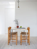 Slender dining table with four chairs in front of white wall