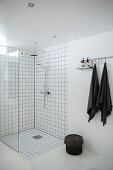 Floor-level shower in white bathroom with black accessories