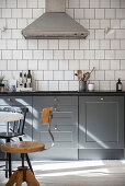 Grey cabinets and white square wall tiles in classic kitchen