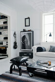 Pallet table and picture of guitar in black-and-white living room