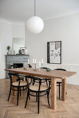 Black bistro chairs around dining table and open fireplace in period building