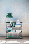 Ornaments in shades of blue and green on metal shelves against distressed wall