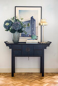 Vase of hydrangeas and picture on Oriental console table