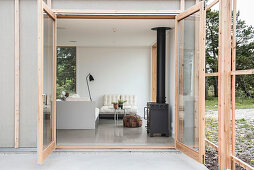 View through open terrace doors into simple living room with wood-burning stove