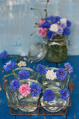 Blue, white, and pink cornflowers in mason jars