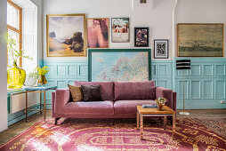 Purple velvet sofa against pale blue panelled wainscoting below gallery of pictures