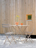 Metal garden table and chairs next to external wall of house made from pale wood