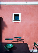 Table and chair in front of small window in pink façade