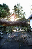 Vintage-style garden furniture decorated for winter with branches and candle lanterns