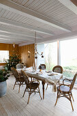 Set dining table and bamboo chairs in festively decorated interior