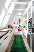 Kitchen with green rug and view into living room of attic apartment