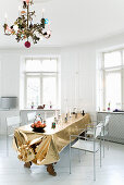 Golden tablecloth and chandelier in white dining room