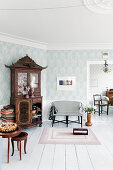 Antique cabinet, pale blue wallpaper and white floor in living room