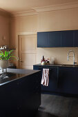 Dark blue, modern kitchen with dark floor and beige walls