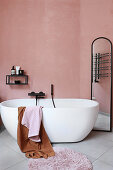 Oval, free-standing bathtub and full-length mirror in pink bathroom