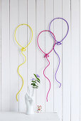 Wall decorations shaped like balloons made from wire and knitted tubes