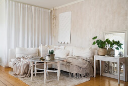Blankets on corner sofa in beige, Bohemian-style living room