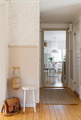 Stool against wall with dado in hallway with wooden floor