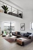 Grey corner sofa in modern, open-plan interior with gallery