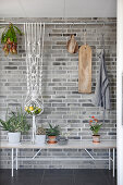 Fruit bowl in macrame hanger suspended from rod in front of brick wall