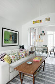 Retro coffee table in front of sofa with colourful scatter cushions in open-plan interior