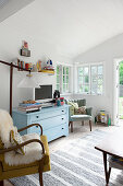 Pale blue chest of drawers in bright, vintage-style living room