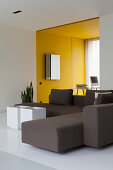 Grey sofa in modern, architect-designed house with yellow alcove