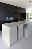 Chairs fitting flush under counter in modern, open-plan ktichen