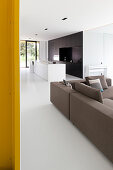 Modern, open-plan interior with white floor and open-plan kitchen
