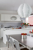 Designer lampshades and dining table in modern, open-plan kitchen