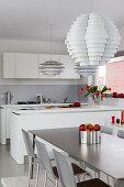 Designerleuchten in der modernen offenen Küche mit Esstisch