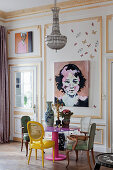 Various chairs around pink table next to paintings on panelled wall