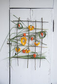 Wall hanging with roses and Chinese reed: Wreaths made of petals and Chinese reed, lampion fruits as decoration