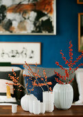Twigs of holly berries in rippled vases in living room