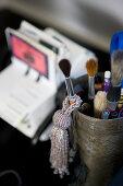 Pot of paintbrushes and beaded tassel on desk