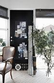 Baroque chair, black pinboard on door and olive branches in floor vase in study