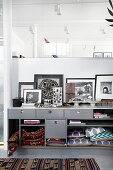 Cushions and kilim rugs stashed in compartments of grey sideboard with black-and-white photographs on top